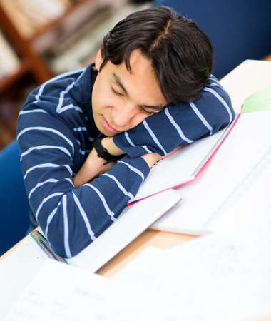 Tired male student sleeping on a pile of books  photo
