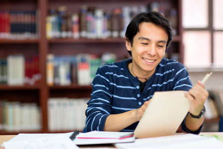 Happy male student at the library reading a book  photo