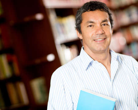 hispanic student: Antiguo alumno universitario masculino sonriente en la biblioteca