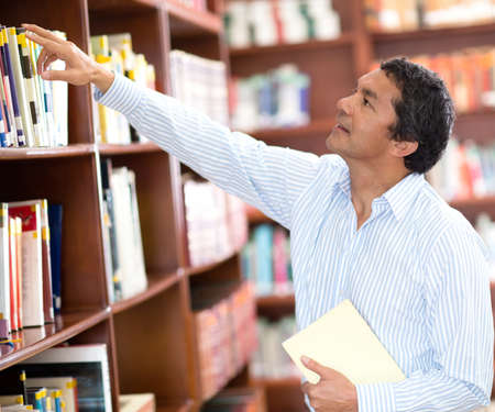 librarian: Teacher at the library looking for a book in the bookshelves Stock Photo