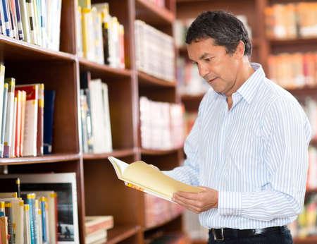 tutor: Ocasional hombre en la biblioteca leyendo un libro Foto de archivo