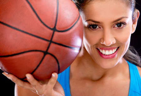 basketball background: Beautiful woman portrait holding basketball and smiling