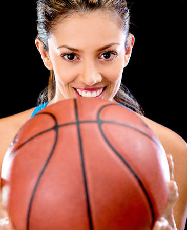 Female basket player holding a ball and smiling  photo