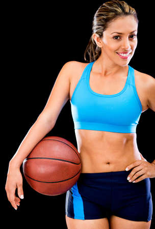 Fit woman playing basketball - isolated over a black background  photo