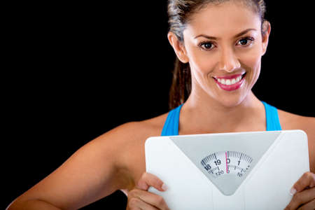 over weight: Woman happy with her weight holding a scale - isolated over black background  Stock Photo