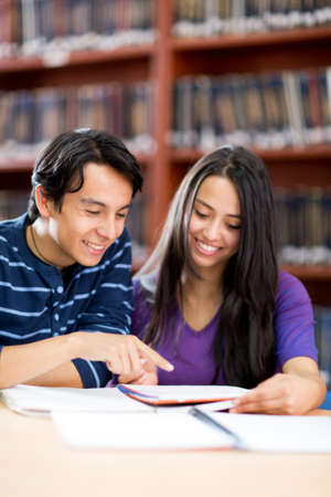 Young people studying at the library and smiling  photo