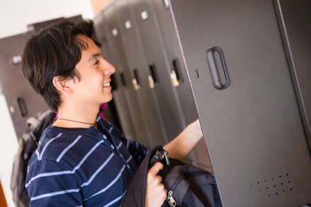 Male student putting things in his locker  photo