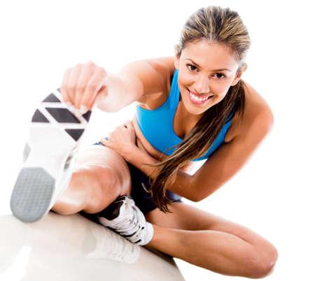 warm up: Fit donna si estende la sua gamba per riscaldarsi - isolato su sfondo bianco