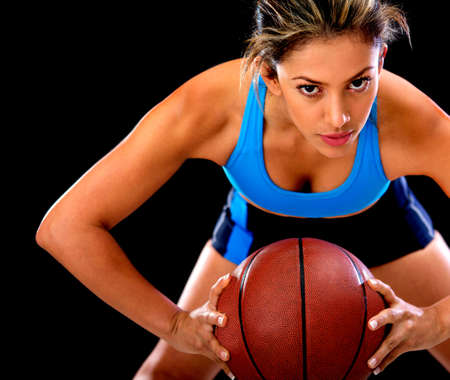 Competitive basketball player holding the ball - isolated over black background  photo