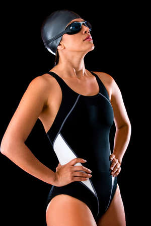 Professional female swimmer in a swimsuit wearing goggles and hat  photo
