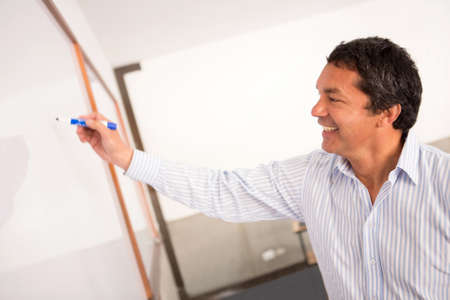 Male college teacher writing on the board and smiling  photo