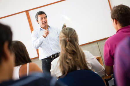 teacher in class: Group of students in class paying attention to the teacher  Stock Photo