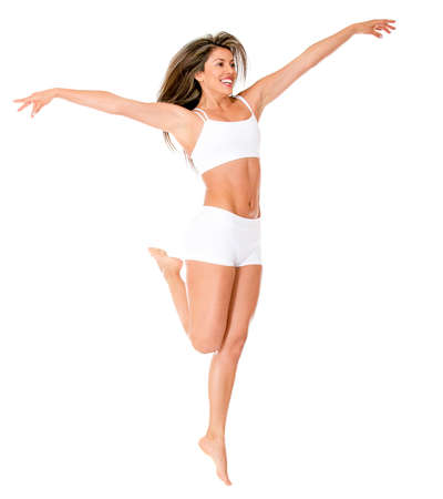 Fit woman in her underwear jumping - isolated over a white background  photo