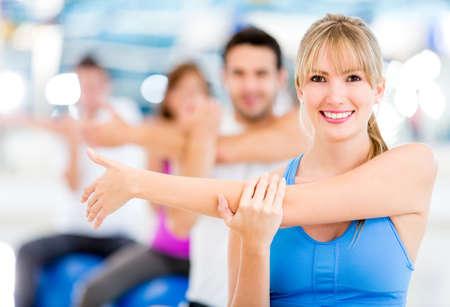 men exercising: Grupo de personas haciendo ejercicio en el gimnasio y se extiende