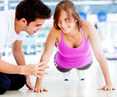 'personal beauty': Woman exercising at the gym with her personal trainer