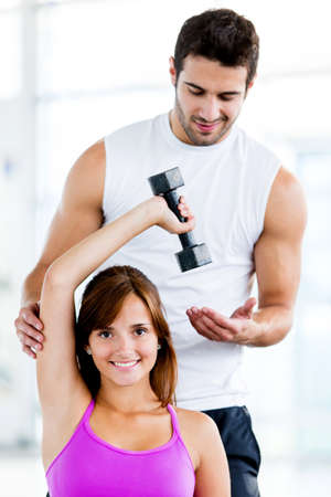 Fit woman at the gym with a personal trainer  photo