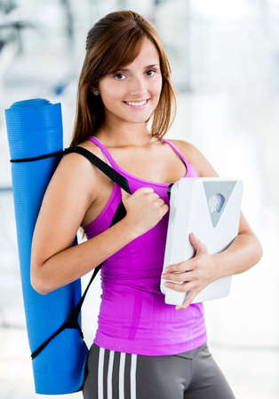 Fit woman with gym mat and holding a scale  photo