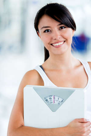 Fit woman with a scale at the gym  photo