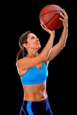 Female basketball player shooting the ball - isolated over black  photo