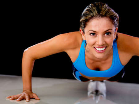 skinny woman: Determined fit woman exercising by doing push-ups
