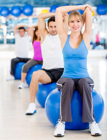 swiss ball: Group of people exercising at the gym and stretching
