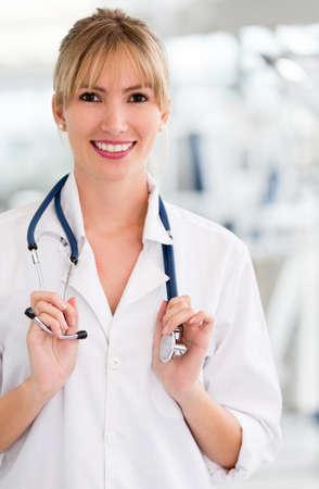 doctora: Amistoso m�dico femenino sonriendo y sosteniendo un estetoscopio Foto de archivo