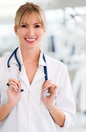 Friendly female doctor smiling and holding a stethoscope  Stock Photo - 14599867