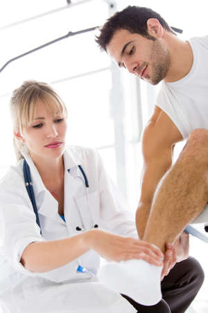 at ankle: Athletic man with an injury in his ankle being checked by a doctor  Stock Photo