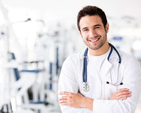 man doctor: Friendly male doctor at the gym smiling  Stock Photo
