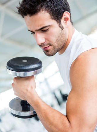 Strong man lifting weights at the gym   photo