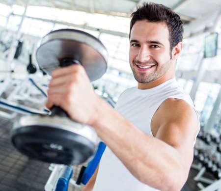 levantar peso: Hombre fuerte en el gimnasio levantando las pesas