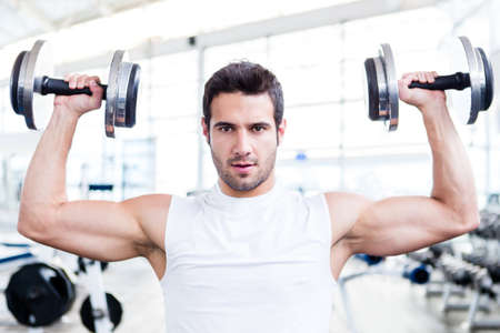 Handsome man at the gym lifting weights  photo