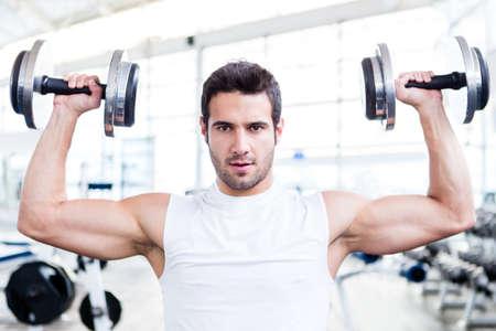 lifting weights: Hombre guapo en el gimnasio levantando las pesas