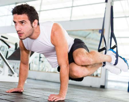 men exercising: Apuesto hombre fuerte ejercicio en el gimnasio