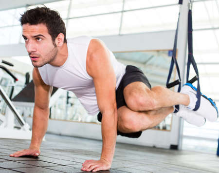 exercise man: Strong handsome man exercising at the gym  Stock Photo