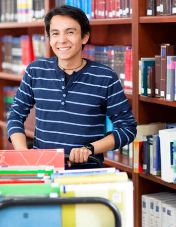 school library: Man working at the library carrying books Stock Photo