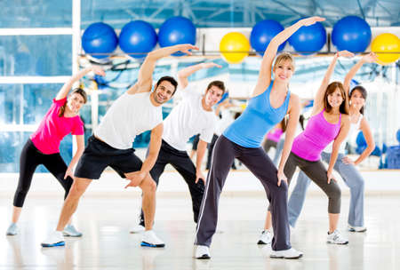 exercise man: Group of people at the gym in a stretching class  Stock Photo