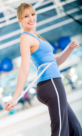 reducing: Woman reducing sizes after exercising at the gym  Stock Photo