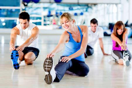 estiramientos: Grupo de personas que se extiende en el gimnasio