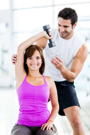 personal training: Woman with a personal trainer exercising at the gym
