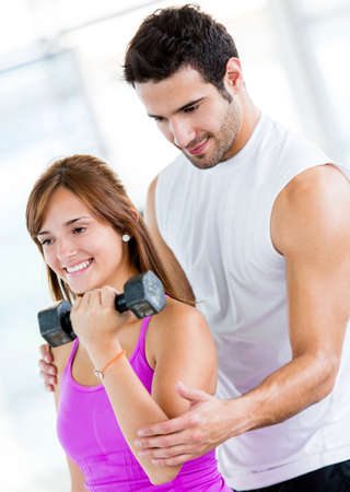'personal beauty': Fit woman at the gym with a personal trainer  Stock Photo