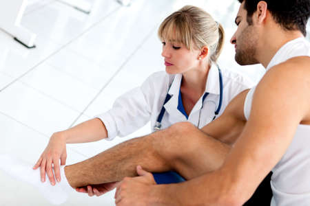 physiotherapist: Gym doctor checking a patient with a hurt ankle  Stock Photo