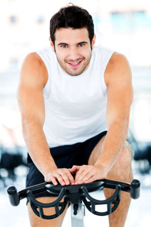 Handsome man cycling at the gym and smiling  photo