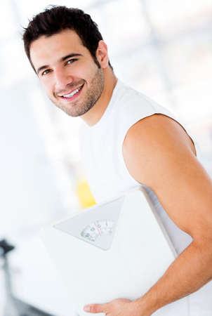 kilograms: Fit man at the gym holding a weight scale