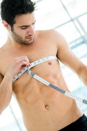 muskelaufbau: Fit Mann Messung seine Muskeln im Fitnessstudio