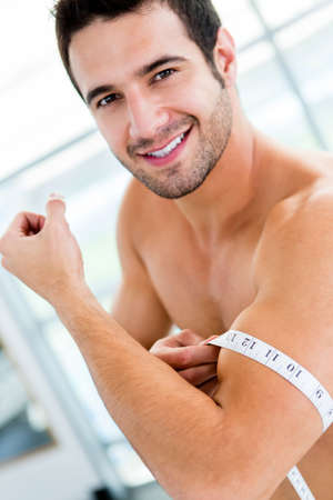 Happy man measuring his muscles at the gym  Stock Photo - 14710104