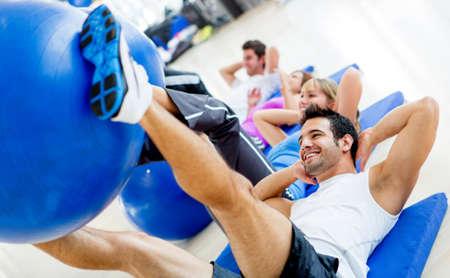 gimnasia aerobica: Grupo de personas gimnasio haciendo ejercicios con pelotas de Pilates