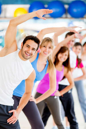 fitness instructor: Group of young people at the gym stretching  Stock Photo
