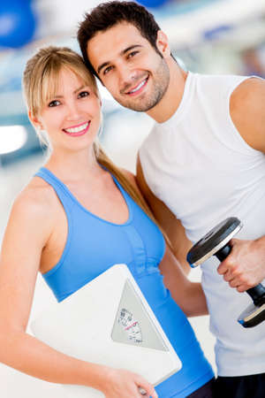 Fit couple at the gym holding a weight scale  photo