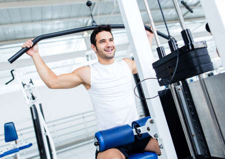 men exercising: Fit man exercising at the gym on a machine  Stock Photo